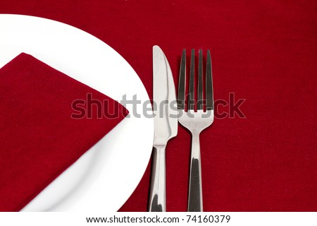 Knife and fork with white plate on red tablecloth