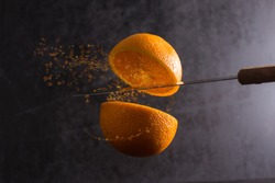 Knife and orange cut in half are frozen in mid air on a black background