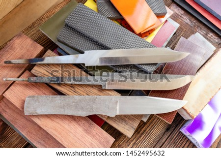 Knife blades, knife handle materials micarta, carbon, G10, acryl composite, wood, brass titanium cooper alloys plates, tubing, pins  for handmade DIY knife making supply wooden background #1452495632