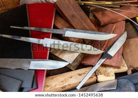 Knife blades, knife handle materials micarta, carbon, G10, acryl composite, wood, brass titanium cooper alloys plates, tubing, pins  for handmade DIY knife making supply wooden background #1452495638