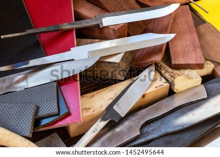 Knife blades, knife handle materials micarta, carbon, G10, acryl composite, wood, brass titanium cooper alloys plates, tubing, pins  for handmade DIY knife making supply wooden background #1452495644