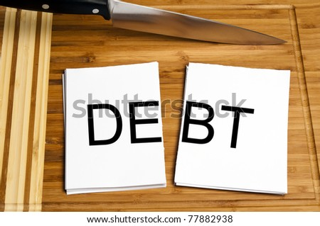 Knife cut paper with debt word