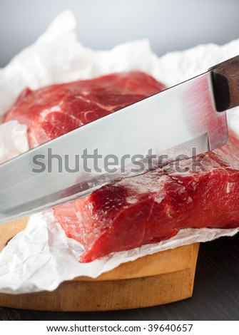 Knife cutting a large piece of uncooked beef