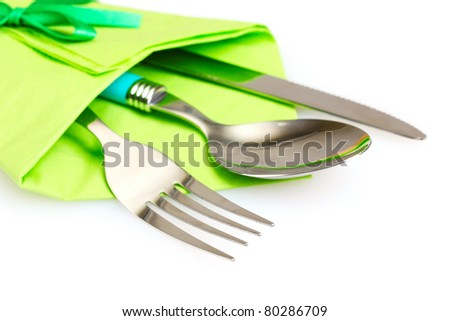 knife, fork and spoon in green cloth, isolated on white