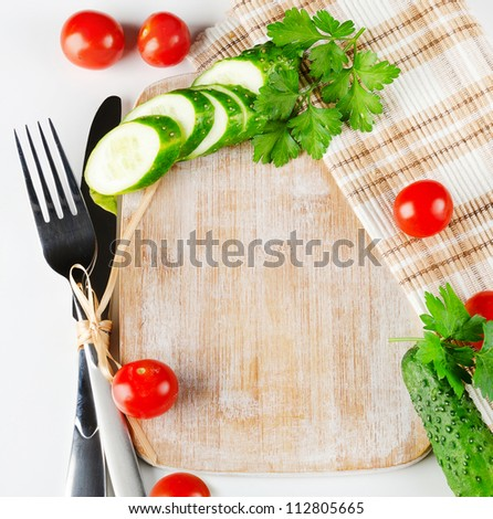Knife , fork and wood cutting board with fresh vegetables