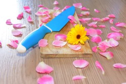 Knife placed on a butcher with yellow flowers.whith rose petals.