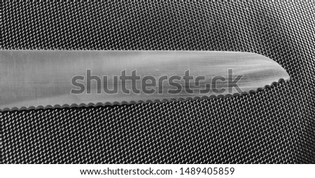 Knife. Sharp chopper with metal texture on black mesh pattern background. Kitchen utensil with threatening notched steel blade. Never needs sharpening. Flat lay photo in concept of cooking or danger.