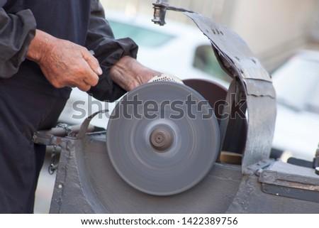 Knife sharpener. Street. Old man's hand. Image.
