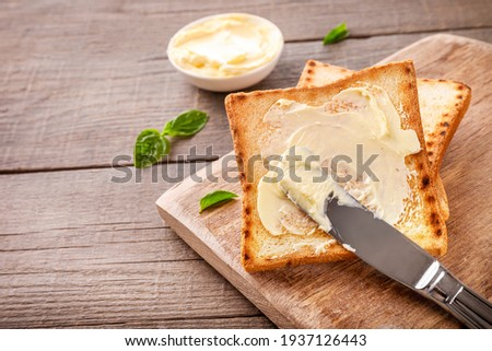 Knife spreading butter on toast bread on wooden background. Copy space. Сток-фото ©