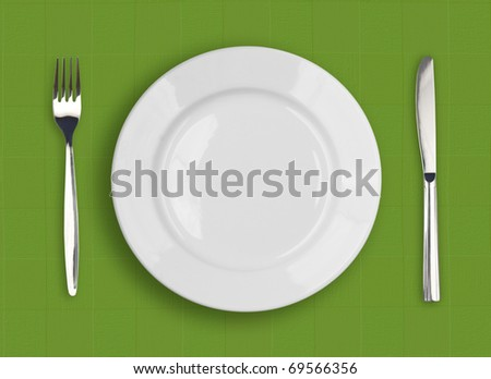 Knife, white plate and fork on green textured background
