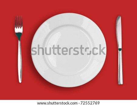 Knife, white plate and fork on red background