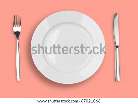 Knife, white plate and fork on rose background