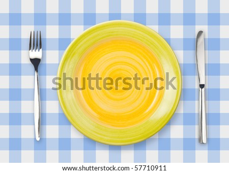 Knife, yellow plate and fork on blue checked tablecloth