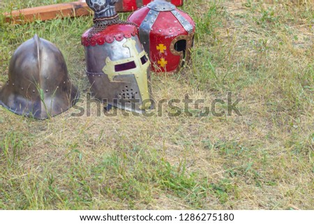Knight helmets on the grass in the field. Reconstruction of medieval combat battles.