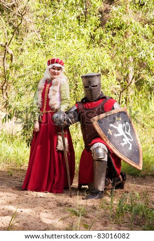 knight in armour and woman in historical costume  at forest