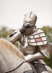 Knight in Shining Armor - medieval renaissance knight in full armor adjusting his face mask while sitting on his horse.