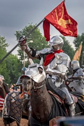 Knight on horseback in medieval steel armor with flag. Historical reconstruction. European warrior of the middle ages, 15th century.
