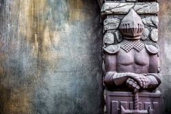 Knight Protectors Stone Statues and Cracked Grunge Wall Background