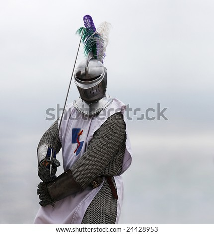 Knight with a sword in mail shirt, armament and helmet (copy space)
