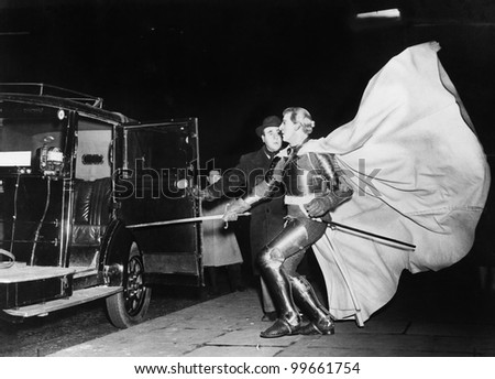 Knight with billowing cape approaching car - stock photo