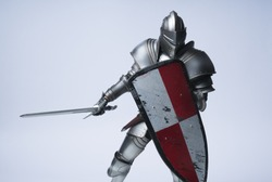 Knight with sword and red checkered shield on isolated background