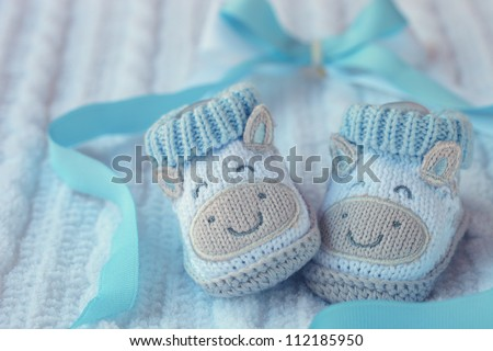 Knitted baby shoes for boy on a blue background. Greeting card.
