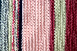 Knitted background, knitted wallpapers, knitted texture. Soft material. Handmade carpet closeup photo. Cozy background.