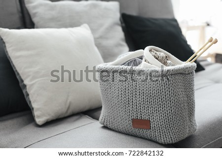 Knitted basket with yarn and needles on grey sofa by cushions. Still life photo of nordic interior details. Cosy place in winter decorated room.