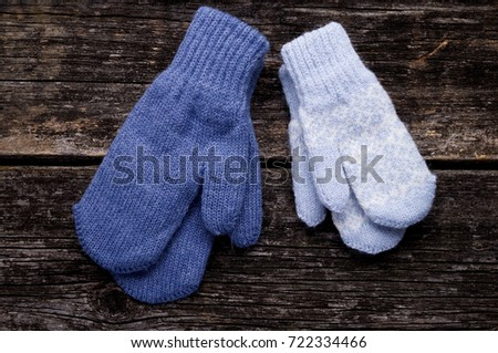 Knitted blue mittens on wood background #722334466