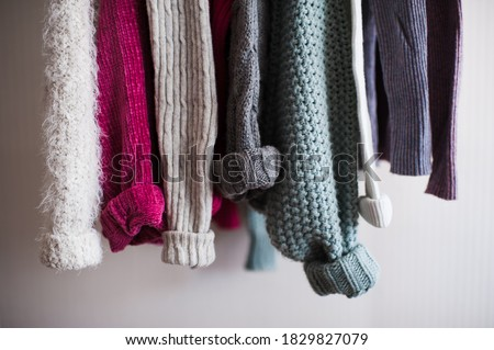 Knitted clothes with folded sleeves hang on hanger indoors closeup. Winter season.  Photo stock ©