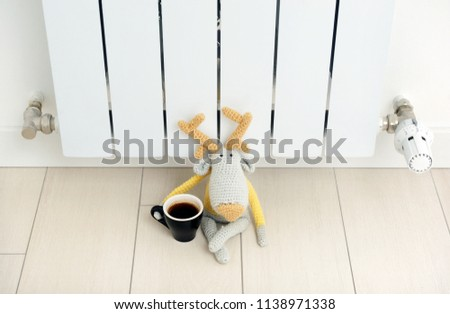 Knitted deer sits on the radiator with a cup in his hand