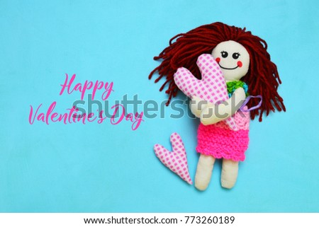 Knitted doll with pink heart on blue background #773260189