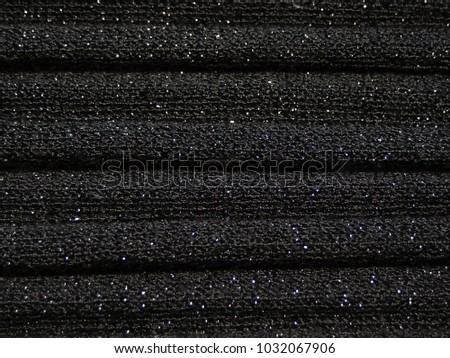 Knitted fabric with waves, black yarn. With a lurex thread. For textures, backgrounds. #1032067906