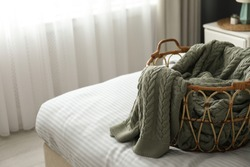 Knitted green plaid in wicker basket on bed indoors space for text.