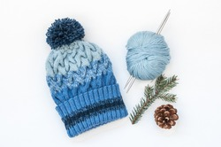 Knitted hand spokes Woolen baby hats with stripes and gradient with a pompon, a skein of yarn and two needles, fir branch and pine corn on a white background.