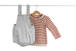 Knitted handmade pullover (sweater) for the baby (boy or girl) and gray overall (shorts) hanging on shoulders isolated on white background for spring/autumn wardrobe/ Baby clothes
