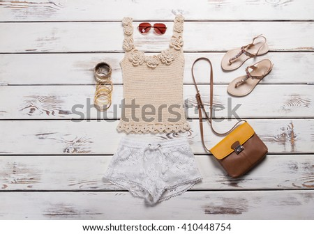 Knitted handmade tank top with sandals. Young woman's outfit on display. Bicolor purse and lace shorts. Leather handbag with summer clothing. #410448754