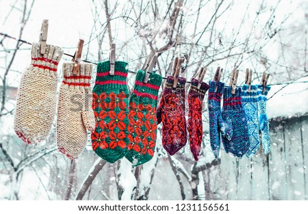 knitted mittens on natural winter background. color mittens hanging by thread in winter day under the falling snow. Winter season symbol. #1231156561