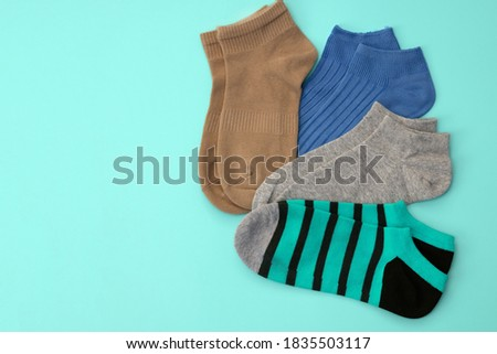 Knitted multicolored short socks on a turquoise background top view. Cotton sports underwear. Set of different socks with copy space. white casual soft socks perfect fit size walking going