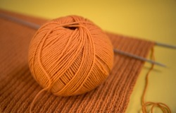 Knitted orange scarf, spokes, yarn on a yellow background. Close. The concept of needlework, knitting, hobby.