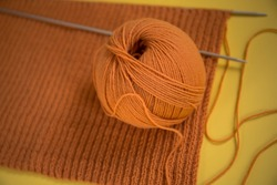 Knitted orange scarf, spokes, yarn on a yellow background. Close, top view. The concept of needlework, knitting, hobby.