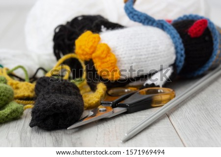 Knitted parts for woolen penguin toy with scissors and knitting needles.  On a grey wood surface.  Craft hobby concept  #1571969494