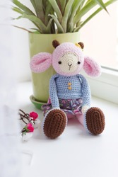 Knitted sheep sits on the window sill.