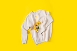 Knitted sweater and autumn flowers on a bright yellow background. Autumn shopping, discount and sale concept. Clothes care, cozy fall. Flat lay. Fall promotion, fashion web line