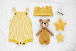 Knitted toy bear, yellow romper and toy stars for newborn on white bed.  Gender neutral  baby stuff and accessories. Flat lay, top view