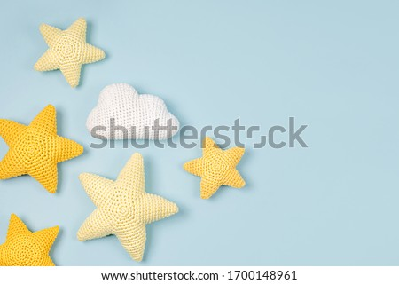 Knitted toy  yellow stars on blue  background. Baby stuff and accessories. Flat lay, top view Stockfoto ©