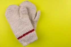 Knitted warm mittens on a yellow background