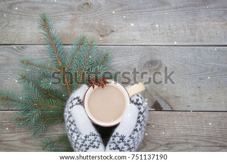 Knitted wool mittens with a cup of coffee cocoa on the wooden background. Rustic style #751137190