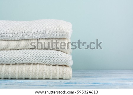 Knitted wool sweaters. Pile of knitted winter clothes on wooden background, sweaters, knitwear, space for text #595324613