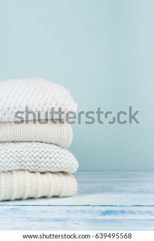 Knitted wool sweaters. Pile of knitted winter clothes on wooden background, sweaters, knitwear, space for text #639495568